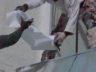 Crew of Roof Menders apply a base coating