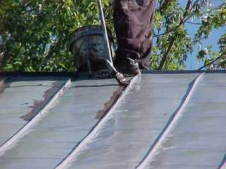 Tin roof paint is being applied by Roof Menders, Inc, starting with crimped seams