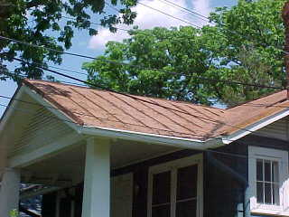 Overhang of trees damaging front panels before process of sealer for tin roof application by crew of Roof Menders