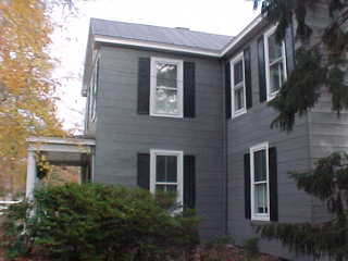 View of color scheme with charcoal siding, black roof and white trim
